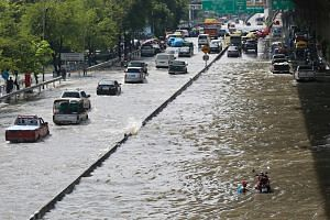 Vehicles driving through a flooded road in Bangkok, Thailand, on Oct 14, 2017. The city has also taken measures to prepare for the coming rain, including clearing all canals and drainage paths and putting water drainage staff on standby to prepare fo