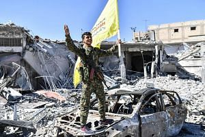 A member of the Syrian Democratic Forces celebrating at Raqqa's Al-Naim Roundabout after the SDF took full control of the Syrian city yesterday. The traffic circle became known as