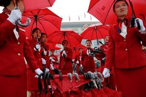 Ushers managing umbrellas used by delegates arriving for the opening session of the 19th National Congress of the Communist Party of China at the Great Hall of the People in Beijing on Oct 18, 2017.