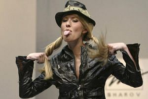 Russian TV host Ksenia Sobchak presents a creation of Russian designer Andrei Sharov during the Fashion Week show in Moscow, Russia, on May 23, 2003.