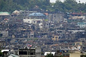 Damaged houses and buildings are seen during a clearing operation in Marawi city, southern Philippines, on Oct 18, 2017.