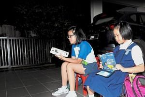 Early risers: Chen Xiao Ni (right), nine, and her sister Xiao Ting, 12, reading a book as they wait for their school van at the front porch of their home in Taman Impian Molek, Johor Baru.