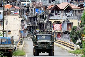 Soldiers driving a military truck through the war-torn city of Marawi yesterday. Defence Secretary Delfin Lorenzana estimates the Philippine government will need $1.5 billion to rebuild the city, which was liberated from terrorists after a nearly fiv