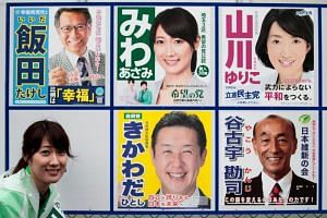 In this picture taken on Oct 20, 2017, Party of Hope candidate and former flight attendant Asami Miwa poses next to portraits of her and other candidates in Koshigaya city, Saitama prefecture. Waving her white-gloved hands and bowing to potential vot