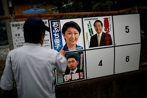 A local resident looks at candidates' posters for the Oct 22 lower house election in Nanmoku Village, north-west of Tokyo, Japan on Oct 12, 2017.