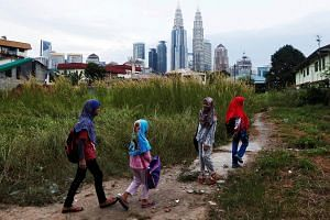 A group of girls make their way home after school in Kuala Lumpur, Malaysia.