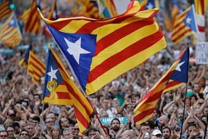 Protesters wave pro-independence Catalan Estelada flags during a demonstration in Barcelona, Oct 21, 2017.