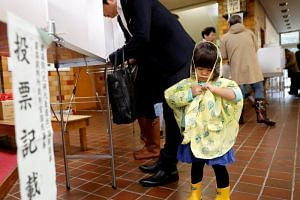 A girl stands next to her father filling out his ballot for a national election at a polling station in Tokyo, Japan October 22, 2017.