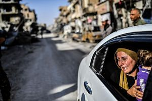 A woman cries while being driven through Raqqa last Friday, after a Kurdish-led force expelled ISIS militants from the northern Syrian city. The fall of Raqqa and the defeat of militants in Marawi might have dealt a major blow to ISIS, but Asian capi