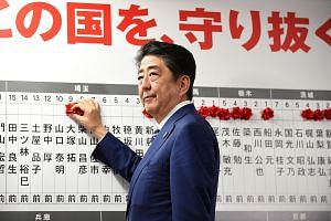 Japanese Prime Minister Shinzo Abe placing rosettes above the names of successful election candidates on a board at the LDP headquarters in Tokyo yesterday. The LDP and its coalition partner Komeito have secured 312 of the 465 Lower House seats, with