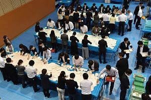 "Officials counting ballot papers at an election office in Tokyo yesterday. The LDP-led coalition has secured a two-thirds ""super majority"" in the powerful Lower House of Parliament."