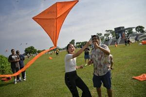 Ms Tiziana Tan, 23, and her husband, Mr Suraj Upadhiah, 29, trying to get the kite into flight at the first Racism Go Fly Kite eventat the Marina Barrage on Oct 22, 2017.