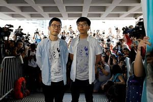 Student leaders Nathan Law and Joshua Wong arrive at the High Court to face verdict on charges relating to the 2014 pro-democracy Umbrella Movement, in Hong Kong.