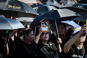 A woman holds an image of the late Thai King Bhumibol Adulyadej during the final dress rehearsal for his funeral in Bangkok on Oct 21, 2017.