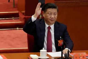 Chinese President Xi Jinping raises his hand as he takes a vote at the closing session of the 19th National Congress of the Communist Party of China at the Great Hall of the People, in Beijing.