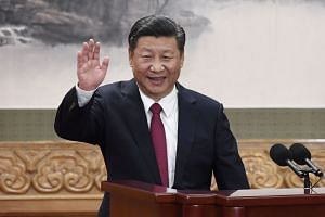Chinese President Xi Jinping waving to party members after unveiling the members of the new Politburo Standing Committee on Oct 25, 2017.