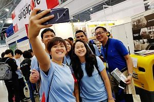 Singapore Polytechnic student Emma Tan Xin Rong (centre, with long hair), 17, posing for a picture with fellow students and senior lecturer Teo Kian Hun at the Singapore Construction Productivity Week trade show.