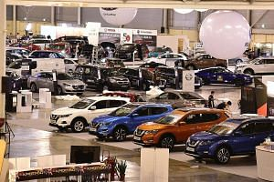 Workers setting up displays on the eve of Cars@Expo, SPH's two-day auto retail bazaar, which starts today. A wide range of sedans, sport utility vehicles, luxury cars and hybrid vehicles are for sale.
