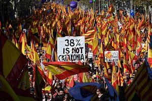 Protesters wave Spanish and Catalan Senyera flags at a during a pro-unity demonstration in Barcelona.