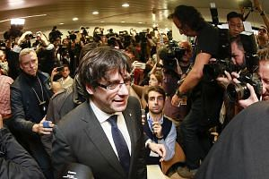 Dismissed Catalonian regional president Carles Puigdemont arriving at the Press Club in Brussels yesterday. He is in Belgium in an effort to evade arrest on charges of sedition filed against him back home in Spain.
