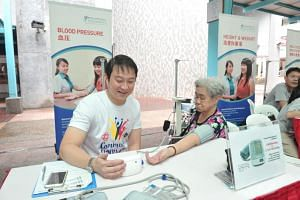 File photo of Dr Lam Pin Min checking the blood pressure of an elderly person during a health event in his constituency.