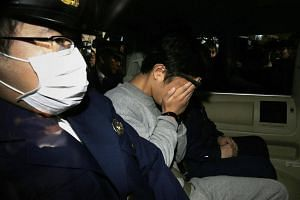 Takahiro Shiraishi covers his face with his hands as he is transported to the prosecutor's office from a police station in Tokyo.