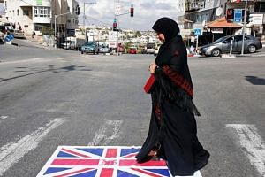 A Palestinian woman walks over a Union Jack flag in Halhul, north of the West Bank town of Hebron on Nov 2, 2017.