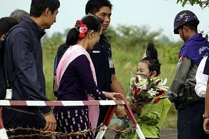 Ms Aung San Suu Kyi receiving flowers from a girl at Sittwe Airport in Rakhine state yesterday. Ms Suu Kyi visited violence-hit Maungdaw and Buthidaung during her one-day trip.