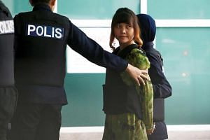 Vietnamese Doan Thi Huong is escorted as she arrives at the Department of Chemistry in Petaling Jaya, near Kuala Lumpur, Malaysia on Oct 9, 2017.