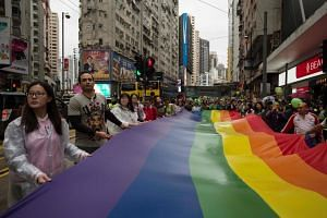 Participants of Hong Kong's annual pride parade walk through the streets with a large rainbow flag.