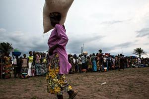 A Congolese woman carries a sack of food onto her head at a food distribution.