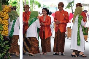 Indonesia's President Joko Widodo (second from right), First Lady Iriana Widodo and sons Gibran Rakbuming Raka and Kaesang Pangarep shake hands with guests while holding a traditional ceremony during preparations for the wedding of Kahiyang Ayu in So