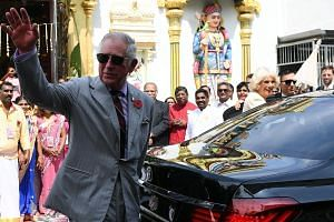 Britain's Prince Charles, Prince of Wales (left) waves to a gathered crowd as Camilla, Duchess of Cornwall (right) smiles after visiting the Sri Mahamariamman Temple in George Town, the capital of Malaysia's Penang state.