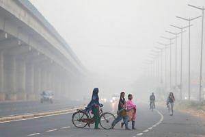 People cross the road in New Delhi.