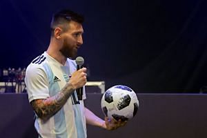 Argentinian national football team striker Lionel Messi poses with Telstar 18, the official match ball for the 2018 Fifa World Cup Russia, during the unveiling ceremony in Moscow on Nov 9, 2017.