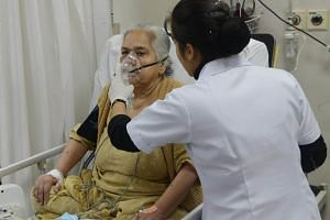 Medical personnel treat a patient using a nebuliser, after she was admitted to the Sri Ganga Ram hospital suffering from the effects of pollution in New Delhi.