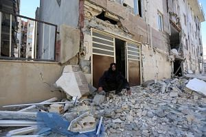 A man sits outside a damaged building following an earthquake in Sarpol-e Zahab county in Kermanshah, Iran on Nov 13, 2017.