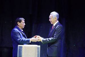 Prime Minister Lee Hsien Loong receiving the ceremonial gavel from Philippine President Rodrigo Duterte to symbolise the passing of Asean leadership, in Manila on Nov 14, 2017.