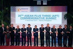Prime Minister Lee Hsien Loong poses for a photo with other Asean leaders and dialogue partners at the 20th Aseab Plus Three Summit.