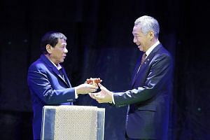 Philippine President Rodrigo Duterte giving Prime Minister Lee Hsien Loong a symbolic gavel to mark the handover of the rotating Asean chairmanship to Singapore at last night's closing ceremony for the 31st Asean Summit.