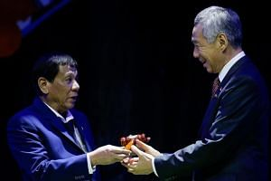 Philippine President Rodrigo Duterte hands over the gavel to Singapore Prime Minister Lee Hsien Loong during a transfer of Asean Chairmanship at the closing ceremonies of the 31st Asean Summit and Related Summits in Manila.