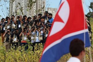 Photographers stake their positions on a hill to get the best shots of the North Korean flag being raised during the team welcome ceremony for the 17th Asian Games Incheon 2014.