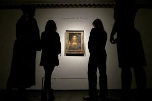 Members of Christie's staff pose for pictures next to Leonardo da Vinci's Salvator Mundi painting.