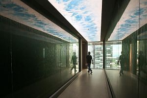 Rest pods that resemble magnetic resonance imaging machines for staff to take 40 winks. A water tunnel (above) with water cascading down the sides of the walkway at the Prudential Singapore office.