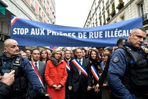 Clichy's mayor Remi Muzeau (centre), and President of the Regional Council of the Ile-de-France region Valerie Pecresse (left), lead a demonstration as they walk under a banner reading