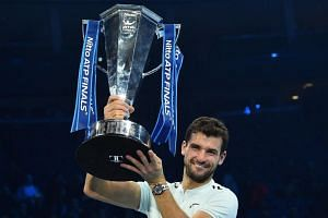 Bulgaria's Grigor Dimitrov holds the trophy as he celebrates winning his men's singles final match against Belgium's David Goffin at the ATP World Tour Finals tennis tournament at the O2 Arena in London on Nov 19, 2017.