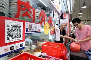 A hawker stall at Tanjong Pagar Plaza Food Centre which accepts cashless payments. Soon, a single QR code from e-payment stalwart Nets will be compatible with the e-wallets of seven major banks - eliminating the need to fuss over which banking app to