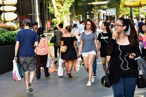 Shoppers seen carrying shopping bags along Orchard Road.