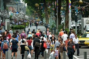 Shoppers in Orchard Road at the junction near Takashimaya.