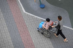 A file photo of a caregiver pushing an elderly on a wheelchair.